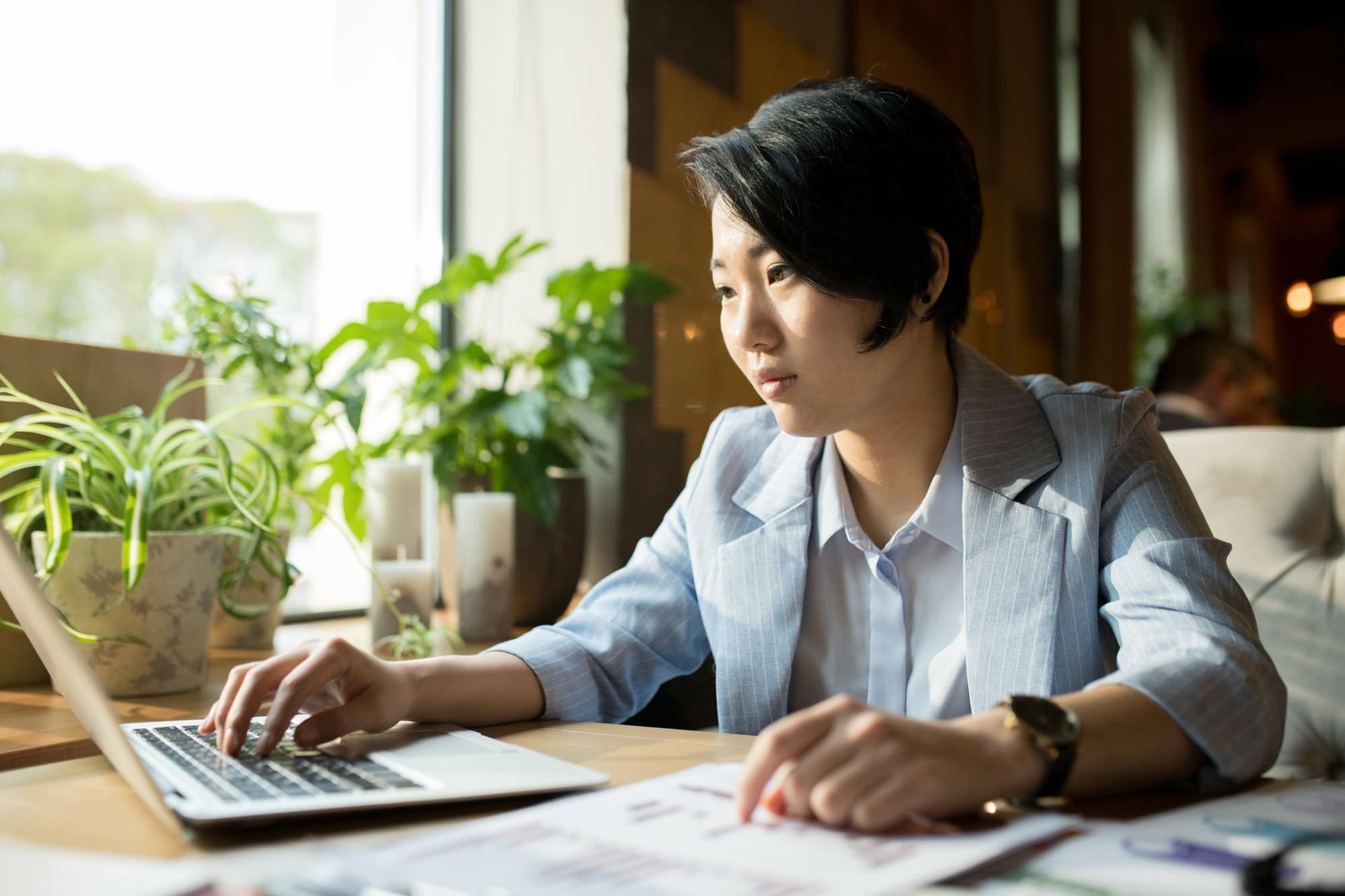 Serious Asian businesswoman comparing information