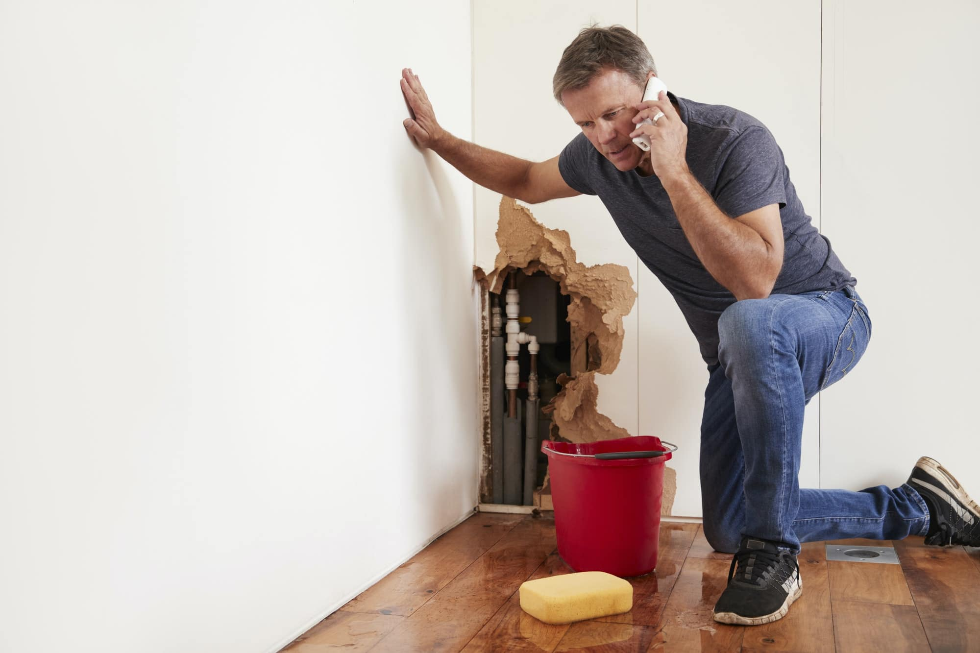 Middle aged man with a burst water pipe phoning for help